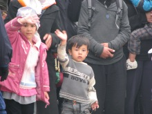 Migrant children wave for the camera.